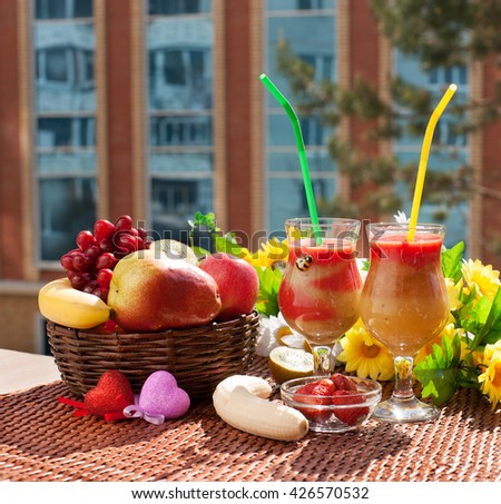 A useful mix of pulp strawberry, apple, kiwi and pears on the balcony. Next to a cocktail  are components of a cocktail. Two toy heart and two glasses mean that these cocktails for two people. - stock photo