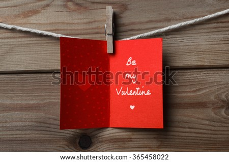 A Valentines Day card , pegged on to string against wood plank background. Opened to reveal decorative hearts and the words 'be my valentine' written inside. - stock photo