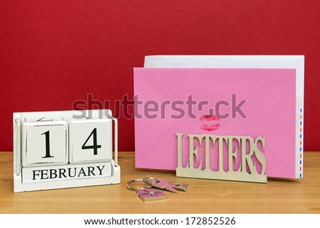 A Valentines day card sealed with a red lipstick kiss in a letterack, with a date block showing 14th February. - stock photo