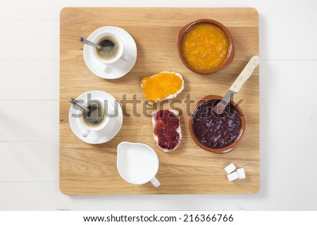 A varied breakfast on wood table with two cup of coffee, milk, two toast with homemade jam and cubes of sugar - stock photo