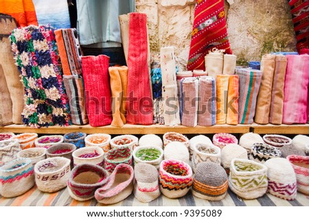 A variety of colored carpets and hats from Northern Africa. Morocco, Essaouira. - stock photo
