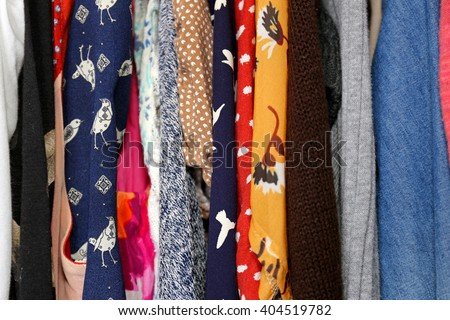 A variety of colorful women's clothing and dress of different fabrics, materials and patterns are hanging in the closet. - stock photo