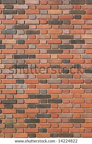 A variety of different color brick in a new brick wall.