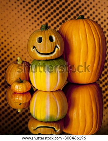 A variety of five stacked pumpkins and their reflection on a on an orange and black spotted background.  One pumpkin has happy carved face. - stock photo