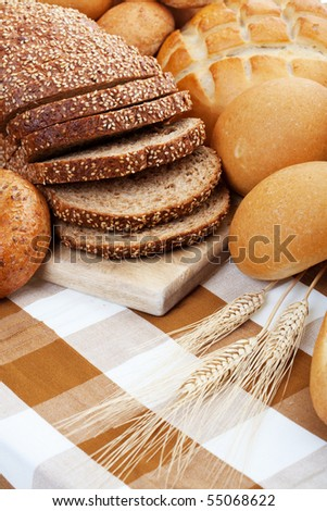 A variety of freshly baked breads along with three stocks of wheat.  Shallow depth of field. - stock photo