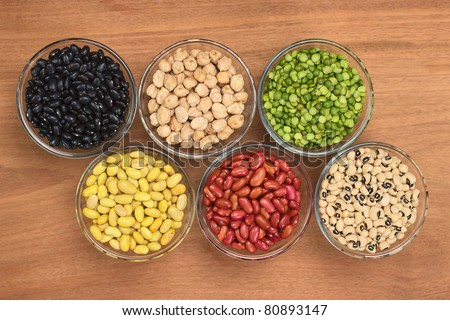 A variety of legumes (black beans, chickpeas, slit peas, canary beans, kidney beans and black-eyed peas) in glass bowl photographed on wood from above - stock photo
