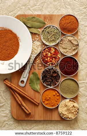 a variety of spices on a bamboo board - stock photo