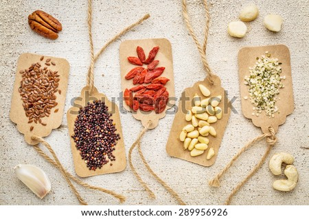 a variety of superfood (nuts, berries, grain, seed) on paper price tags against grunge barn wood background - stock photo
