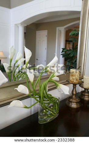 A vase full of calla lilies in a home interior - stock photo