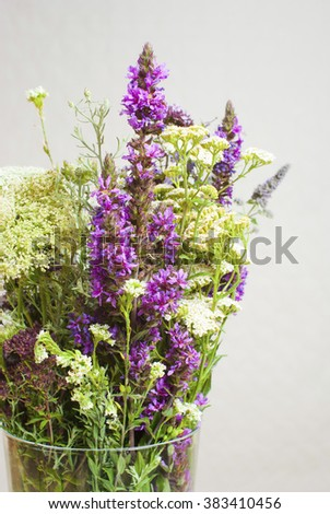 a vase of wildflowers on white wooden table