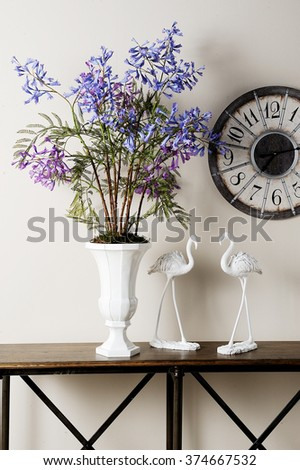 a vase with a clock and plush storks in a buffet