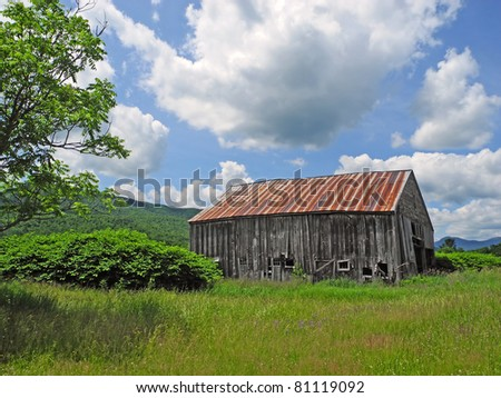 A vast fair-weather sky and vintage barn on lush farmland, paint a picturesque scene of rural and agrarian Americana. - stock photo