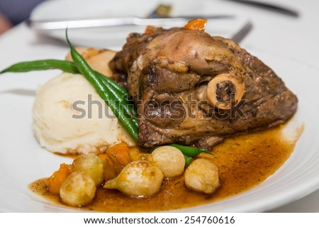 A veal or lamb shank on a plate with gravy, mashed potatoes, green beans and baby onions - stock photo