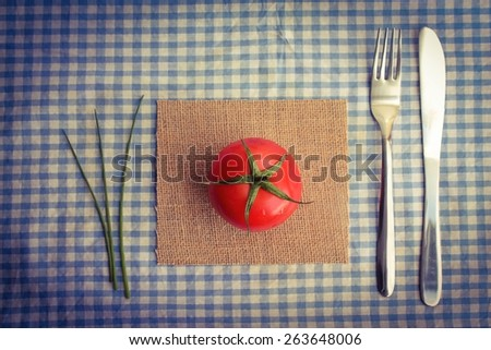 A Vegetarian meal - a fresh red tomato with cutlery and chives on a blue gingham tablecloth - stock photo