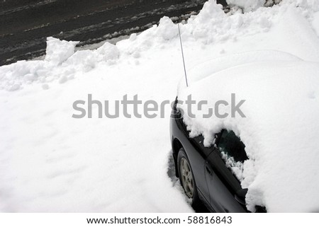 A vehicle covered in snow and snowed in just after the city plow passed the driveway. - stock photo