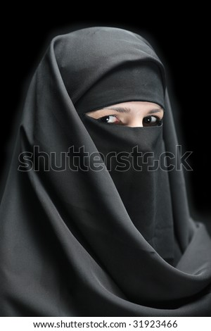 A veiled woman isolated on a black background - stock photo
