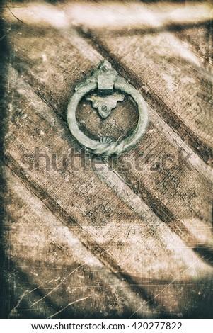 A verdigris door knocker ring on a weathered brown door, textured in a grungy way. - stock photo