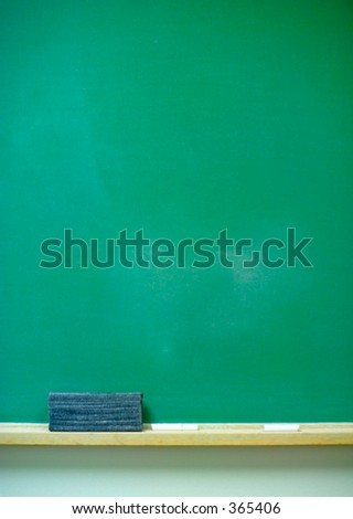 A  vertical green chalkboard with eraser and chalk. 14MP camera. - stock photo