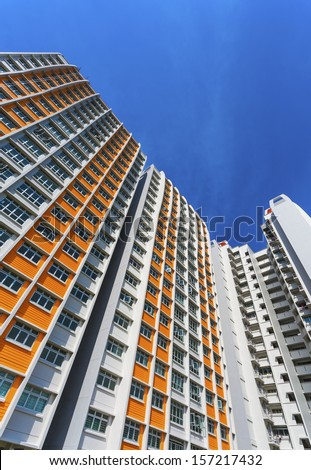 A vertical low angle shot of a new colorful high rise apartment against the sky. - stock photo