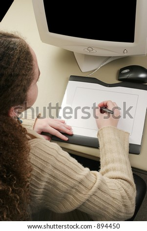 A vertical view of a girl working on a computer graphics tablet.