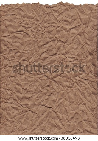 A vertical view of wrinkled kraft paper with a ragged edge - stock photo