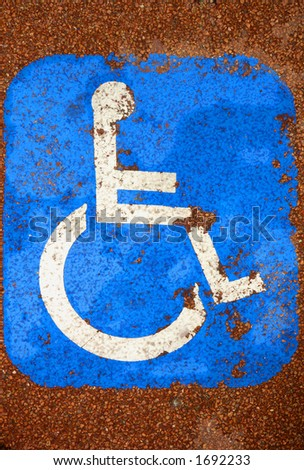 A very battered sign for disabled parking, on red tarmac, giving an impression of disablility (look at the damaged knee). - stock photo