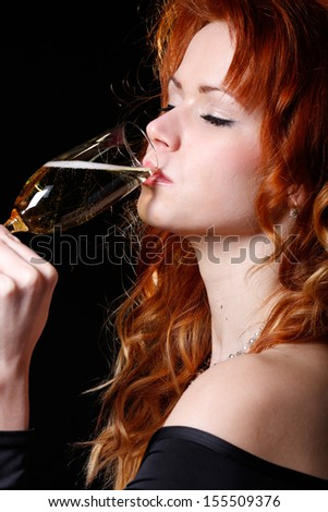 a very beautiful and happy woman dressed in a black dress is holding a glass of champagne in her hands ready to toast