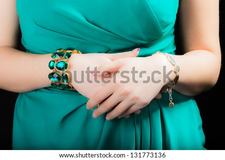 A very beautiful woman in a dress and wearing jewelery posing on a black background - stock photo