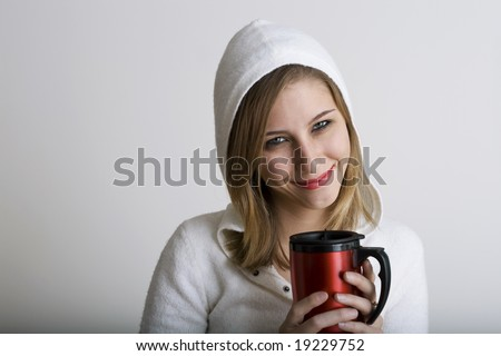 A very beautiful young model is smiling while holding a red holiday thermos - stock photo