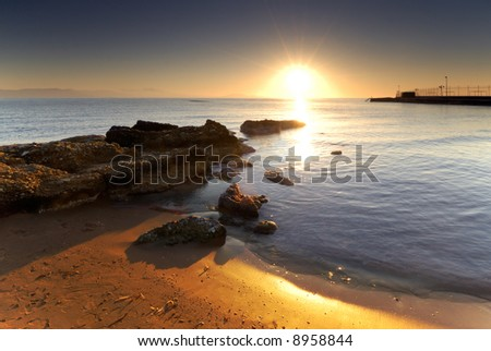A very bright sunrise over a Mediterranean rocky seascape. - stock photo