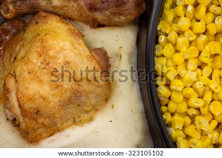 A very close view of a microwaved TV dinner of roasted chicken with mashed potatoes and corn in a black plastic tray. - stock photo