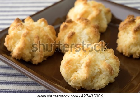 A very close view of sugar free coconut macaroons in a small dish atop a blue striped tablecloth. - stock photo