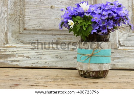 A very cute handmade vase wrapped with natural linen cloth with bouquet of blue wildflowers, simple composition, vintage style, shabby chic