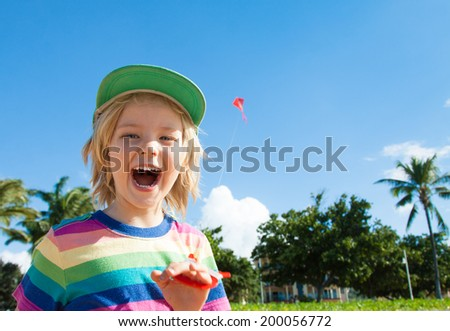 A very excited, cute young boy laughing and flying a kite at the beach. - stock photo