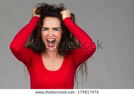 A very frustrated and angry woman is pulling her hair and screaming. - stock photo