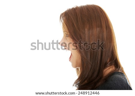 A very frustrated and angry woman screaming. - stock photo