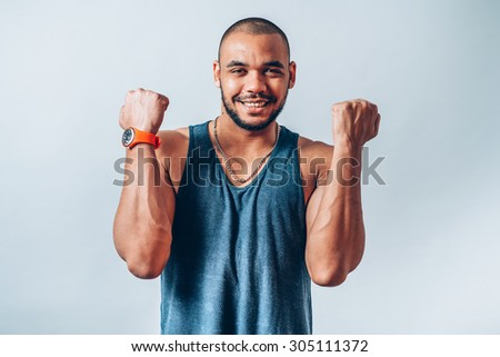 A very happy and attractive african businessman wearing a corporate grey suit and blue tie punching the air with his fists arms in air, smiling and shouting in victorious success for his business deal - stock photo