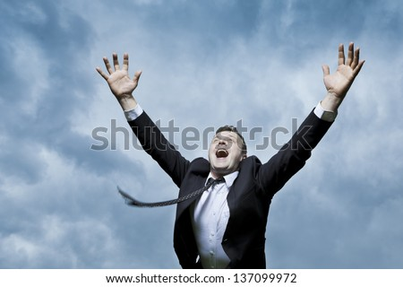 A very happy young man. It turns your joy raising his arms to the sky. He looks up. - stock photo