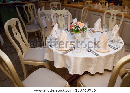 A very nicely decorated wedding table with plates and serviettes.