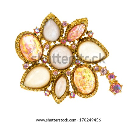 A very old brooch showing details on a white background. - stock photo