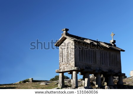 A very old corn drier, made of stone isolated over blue sky background - stock photo