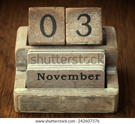 A very old wooden vintage calendar showing the date of 3rd November on wood background