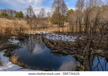 A very picturesque spring landscape on the river with reflection in water,blue sky and white clouds/Beautiful view of river with trees,white clouds,blue sky and reflection in water