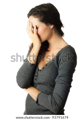 A very sad and depressed woman hiding her face in her hands - stock photo
