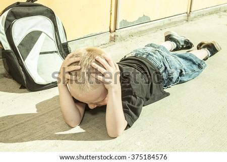 A very sad boy in school playground - stock photo