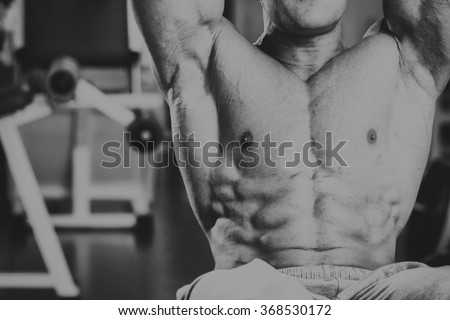 A very strong man is engaged in the gym