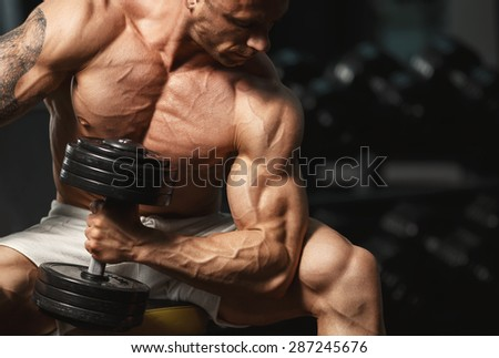 A very strong young guy bodybuilder, doing exercises with dumbbells in the gym. Fitness muscular body on dark background. Sports and fitness. Fitness man in the gym. Fitness man with dumbbell. - stock photo