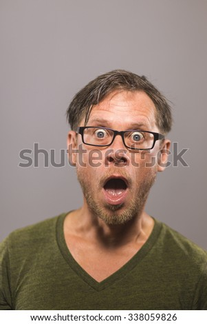 A very surprised man wearing glasses - stock photo
