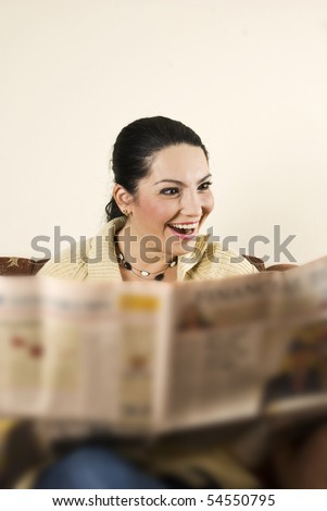 A very surprised woman and happy reading the newspaper  in her sofa in living room - stock photo