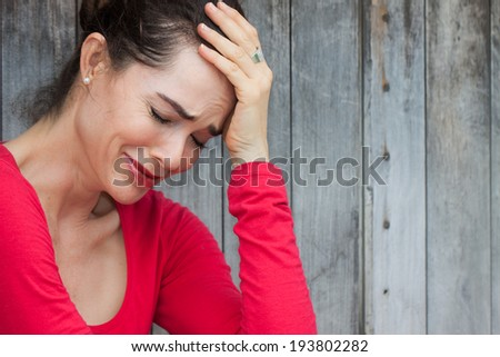 A very upset and lonely woman sitting down crying against a wall - stock photo
